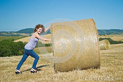 Woman pushing huge bales of hay