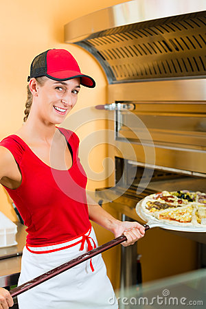 Woman pushing the pizza in the oven