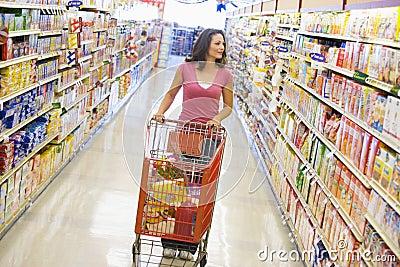 Woman pushing trolley along supermarket aisle