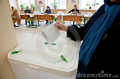 Woman put election ballot into the box Editorial Stock Photo