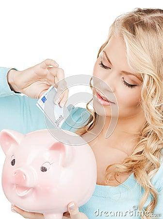 Woman puts cash money into big piggy bank