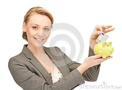 Woman putting cash money into small piggy bank