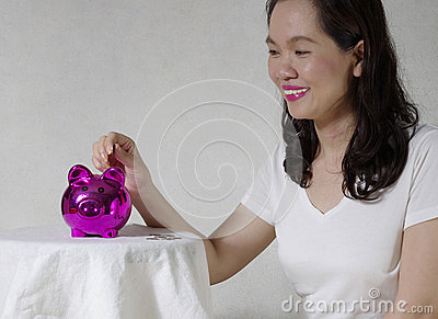 Woman putting a coin into money box