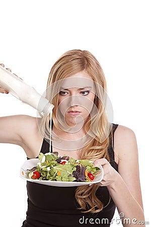 Woman putting dressing on salad