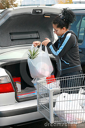 Woman putting groceries in trunk