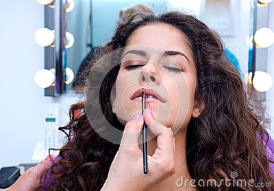 Woman putting lip gloss