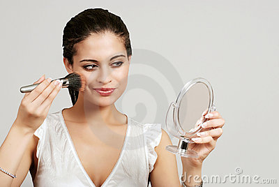 Woman putting on makeup with blush brush