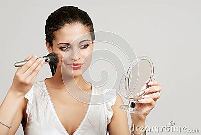 Woman putting on makeup with blush brush