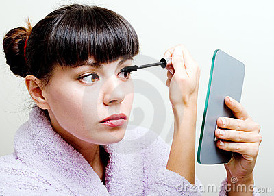 Woman putting mascara
