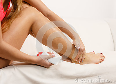 Woman putting ointment on bad ankle applying cream Stock Photo