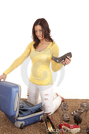 Woman putting shoe in suitcase