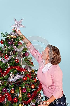 Woman putting star on top of Christmas tree