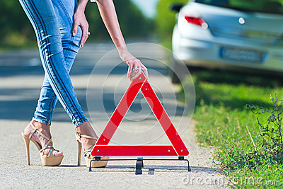 Woman putting a triangle on a road
