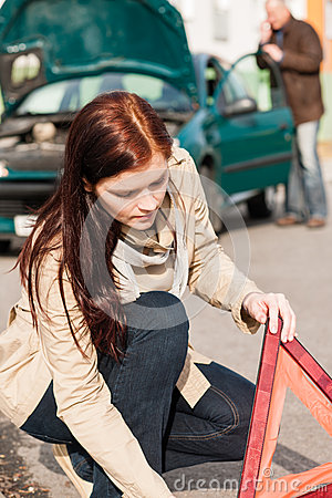 Woman putting triangle sign for car breakdown