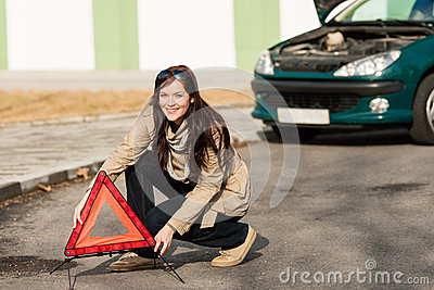 Woman putting warning triangle on the road