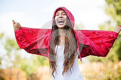 Woman in raincoat enjoying the rain