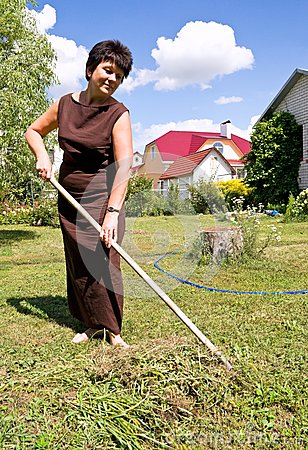 Woman rakes up oblique grass