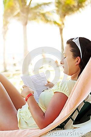 Woman reading book on the Caribbean beach