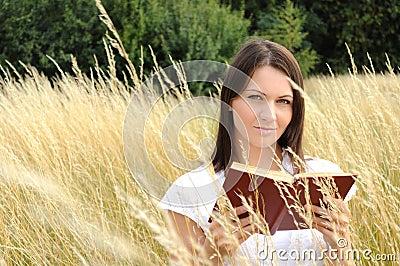 Woman reading book in field