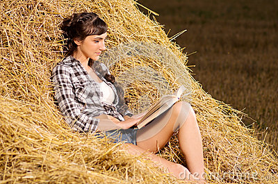 Woman reading book on haystack