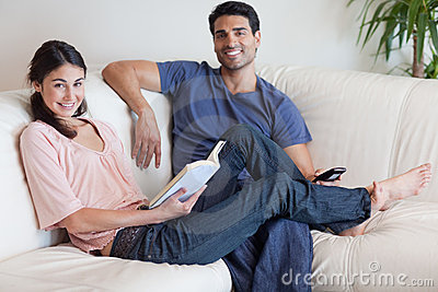 Woman reading a book while her husband is watching TV