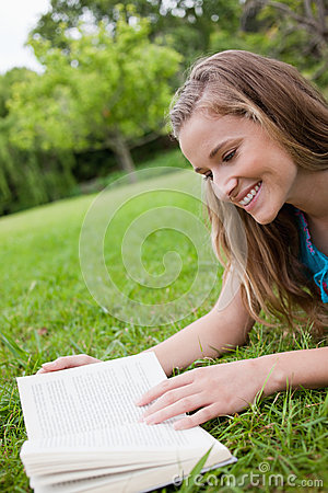 Woman reading a book while lying in a park