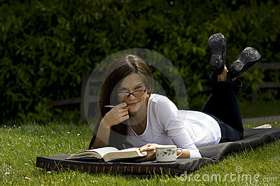 Woman reading book on grass in park