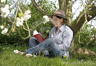 Woman reading a book under a tree