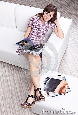 Free Woman Reading Fashion Magazine On Sofa Stock Photo - 10034240