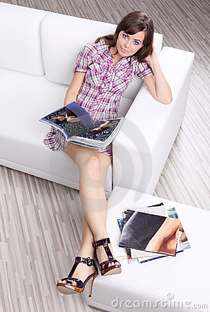 Woman  reading fashion  magazine on sofa