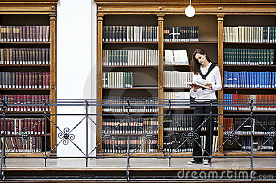 Woman reading in front of bookshelf