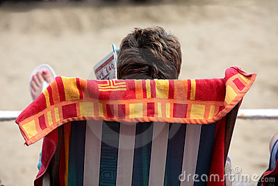 Woman reading magazine on beach in deckchair
