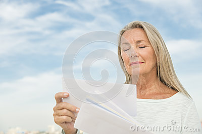 Woman Reading Mails Against Sky