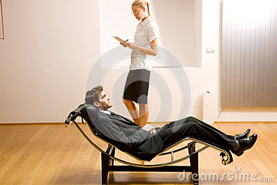 Woman reading man lying on chaise longue
