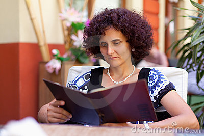 Woman reading menu book in a restaurant
