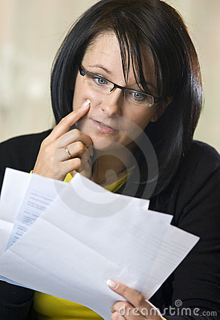 Woman reading pile of bills