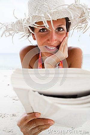 Woman reads a book on beach