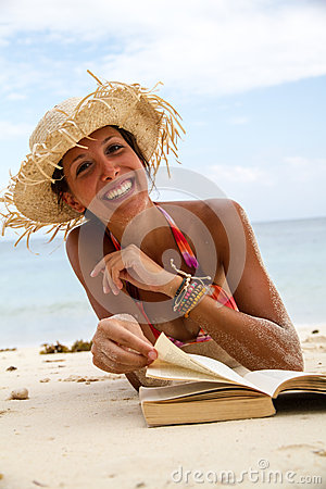 Woman reads a book on beach