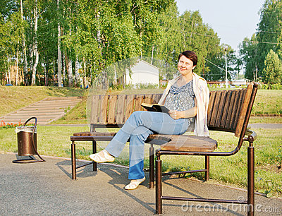 Woman reads a book on a bench