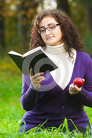 Woman reads book on green grass