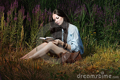 The woman reads the book on the nature