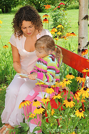 Woman reads book to little girl in garden