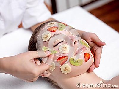 Woman receiving fruit facial mask at spa salon