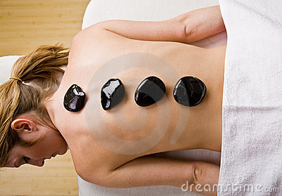 Woman receiving hot stone therapy massage