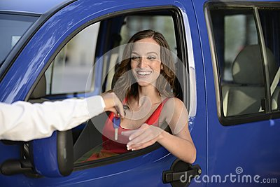 Woman receiving keys of her new car