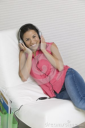Woman reclining on chair Listening to Music on headphones portrait