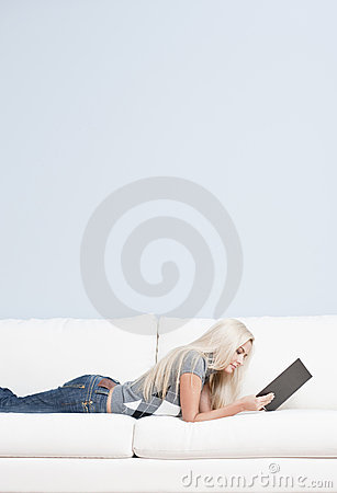 Woman Reclining on Couch With Book