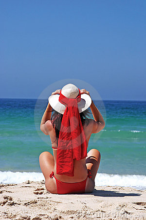Woman in red bikini sitting on beach adjusting hat