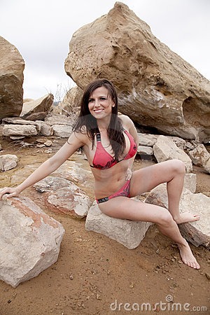 Woman red bikini sitting on rock