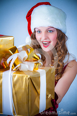 Woman in a red dress and hat of Santa with a big gift